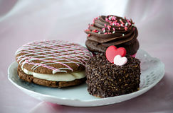 Pastries for your sweatheart. Pink and white chocolate is drizzled over a chocolate cake whoopee pie, filled with white cream, a chocolate cupcake with pink and Stock Photography