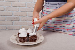 Pastry bag putting cream over cupcake Stock Images