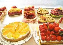 Pastry baked cakes at the bakery. Gorgeous view of different cakes in a bakery, with fruits as strawberries and oranges stock images