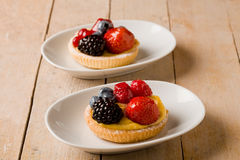Pastry with berries on wooden table Royalty Free Stock Images