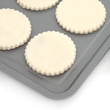 Pastry Biscuit Dough. Pastry biscuit circular cut outs an a baking tray, over white background Royalty Free Stock Image