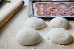 Pastry board rolling pin and dough balls to make the pizza Stock Photo