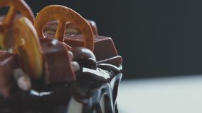 pastry Bolo de creme branco com crosta de gelo do chocolate, chocolate e pretzeis filme