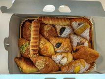 A pastry box filled with cannoli, croissants and croissants royalty free stock photo