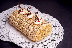 Pastry cake biscuit roulade with whipped cream and chocolate scrolls Stock Photo