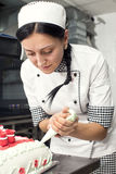 Pastry Cake Decorating. Pastry chef decorates a cake in a candy store Stock Photo