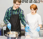 Pastry chef brews dough. She helps him to cook in the kitchen Stock Images