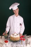 Pastry Chef with Cake. Female Pastry Chef standing with her nearly completed vanilla butter-cream chocolate devil's food cake before transferring to the cake Royalty Free Stock Image