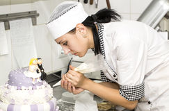 Pastry chef decorates a cake Royalty Free Stock Photography