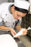 Pastry chef decorates a cake Stock Image