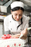 Pastry chef decorates a cake Stock Images