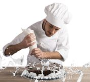 Pastry chef decorating. Pastry chef decorates a cake with cream Stock Photos