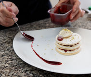 Pastry chef is decorating the dessert with berry sauce stock image