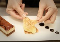 Pastry chef is decorating a dessert Stock Photos