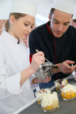 Pastry chef giving student cooking advice Stock Images