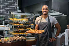 Pastry chef holding small pastry. Smiling black baker with apron holding tray of small pastry and looking at camera. Young african chef holding sweet tray at Stock Images