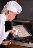 Pastry Chef Inspects Cookies. Passive posed uniformed female Pastry Chef inspects test batch of heart shaped sugar cookies as she is taking them out of the oven Royalty Free Stock Photos