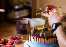 Pastry chef in the kitchen decorating a cake of chocolate,fruit,. Candies,Confectioner is decorating chocolate cake,cooking class, culinary, bakery, food and Stock Photos