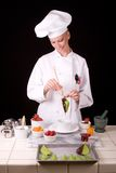 Pastry Chef with leaf. Passive posed uniformed female Pastry Chef standing at her dessert station brushing melted dark chocolate onto a citrus leaf Royalty Free Stock Image