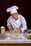 Pastry Chef Lifting Cut Dough. Assertive posed female Pastry Chef lifting heart-shaped cut cookie dough from cold marble dough board Stock Photo