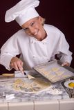 Pastry Chef Loads Cookie Tray. Assertive posed female Pastry Chef loading heart-shaped cut cookie dough from cold marble dough board onto baking tray Royalty Free Stock Photos