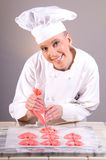 Pastry Chef Piping Hearts. Portrait of a smiling female Pastry Chef piping decorative meringue pink hearts for Valentine's dessert plate Garde Manger Royalty Free Stock Photo