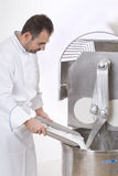 Pastry Chef prepares the ingredients. Pastry Chef pours ingredients into the mixer Stock Image