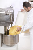 Pastry Chef prepares the ingredients. Pastry Chef pours ingredients into the mixer Royalty Free Stock Photo