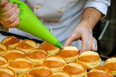 The pastry chef prepares the rolls and lubricate them with cream stock image