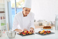 Pastry chef preparing cupcakes Stock Images