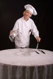 Pastry Chef presenting. Assertive posed uniformed female Pastry Chef presenting at the table-side Royalty Free Stock Image