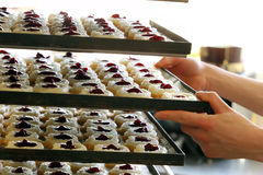 Pastry chef puts cakes in the bakery Royalty Free Stock Photos