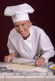 Pastry Chef Rolls Dough. Assertive posed smiling female Pastry Chef rolling cookie dough on cold marble dough board Royalty Free Stock Image