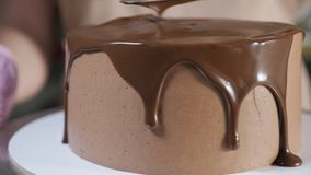 Pastry chef is smearing cake liquid chocolate glaze with knife on the top of the cake to decorate it.