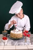 Pastry Chef Spotting Cherry. Female Pastry Chef spotting a cherry atop a star throne of butter-cream on a decorated cake cake Royalty Free Stock Photos