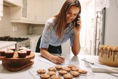 Pastry chef taking orders. Young pastry chef standing at kitchen counter taking order. Happy chef talking on phone and making notes on paper royalty free stock photography