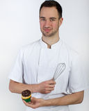 Pastry chef with whisk and cupcake Royalty Free Stock Photos