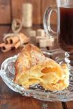 Pastry choux dough with cinnamon and a cup of coffee Royalty Free Stock Images