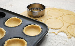 Pastry circles cut and lining a metal bun tin Royalty Free Stock Photo