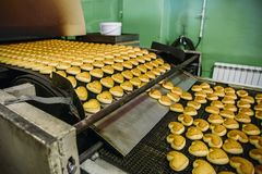 Pastry on conveyor line, food production factory or plant with machinery. Making cookies process.  stock photography