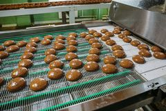 Pastry on conveyor line, food production factory or plant with machinery. Making cookies process.  stock image