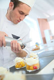 Pastry cook putting the whipped cream on desserts Royalty Free Stock Photos