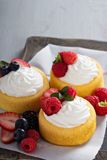 Pastry cups filled with cream and fresh berries Stock Images