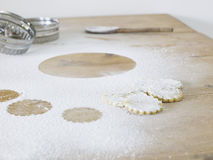 Pastry cutters cookies and flour scattered on table close up Royalty Free Stock Image