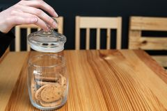 Pastry food cookie woman hand taking biscuit jar. Pastry food. tasty chocolate chip cookies. woman hand removing jar lid to taste some buscuits royalty free stock photo