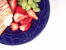 Pastry, Grapes and Strawberry. On a blue plate stock photo