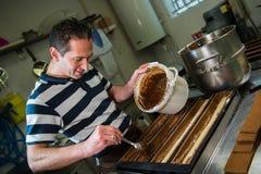 Pastry in his workshop preparing Chocolate Yule logs Stock Image