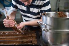Pastry in his workshop preparing Chocolate Yule logs Stock Photo