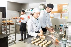 Pastry Makers With Dough In Kitchen. Female pastry cook making dough balls while working with male coworker in kitchen stock images