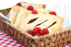 Pastry pockets or mini pies. Danish pastry pockets or mini pies with raspberry filling, honey and almonds Stock Images